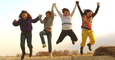nlpaed, Lebensfreude, Kinder halten sich an den Händen und springen in die Luft